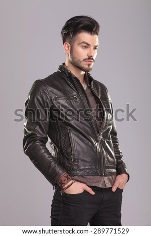 Side view of a young handsome casual man looking away with his hands in pockets. - stock photo
