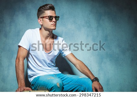 Side view of a young handsome man sitting while looking away. - stock photo