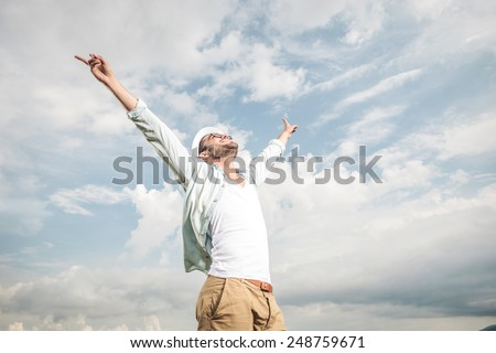 Side view of a young happy man enjoying the good weather, looking up and holding his hands in the air. - stock photo