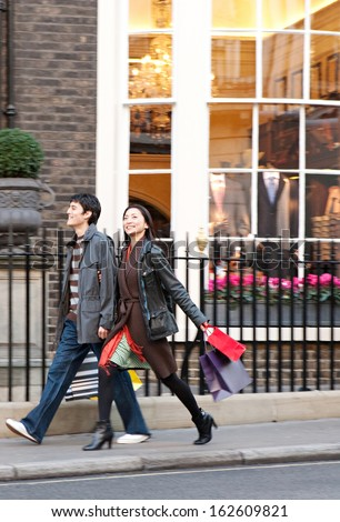 Side view of a young Japanese tourist couple on vacation walking down an exclusive and luxurious shopping street in London city with classic stores and holding carrier paper bags, outdoors. - stock photo