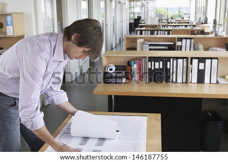 Side view of a young male architect studying blueprint in office