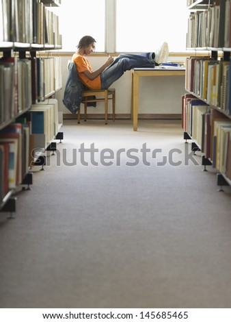 Side view of a young male college student doing homework in the library - stock photo