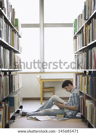 Side view of a young male college student reading in the library - stock photo