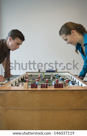 Side view of a young man and woman playing table football in game room - stock photo