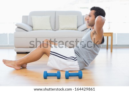 Side view of a young man doing abdominal crunches in the living room at house - stock photo