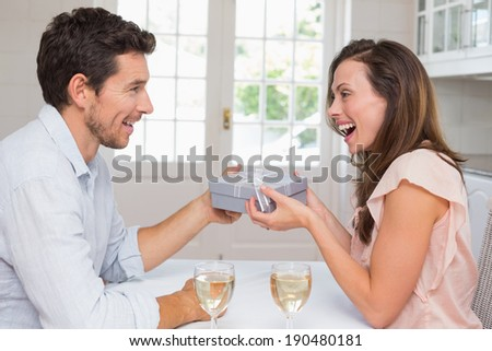 Side view of a young man giving happy woman a gift box at home