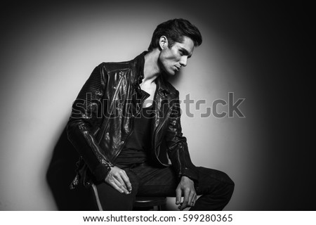side view of a young man in leather jacket resting on a chair