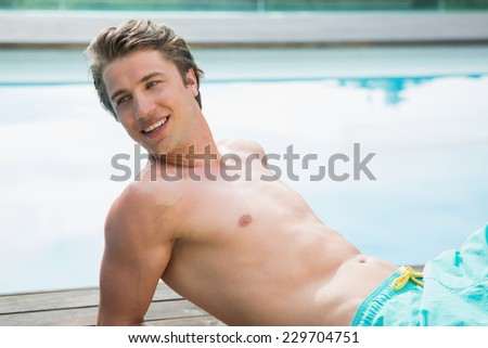 Side view of a young man lying by the swimming pool on a sunny day - stock photo