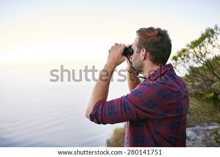 Side view of a young man on a mountain side looking out to the horizon using binoculars