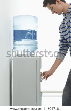 Side view of a young man pouring water from cooler - stock photo