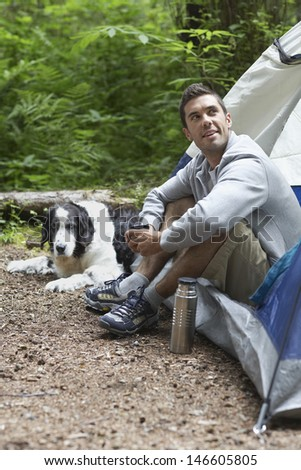 Side view of a young man sitting by tent with dog - stock photo