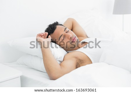 Side view of a young man sleeping in bed at home