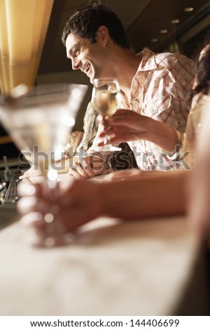 Side view of a young man standing and laughing at the bar - stock photo
