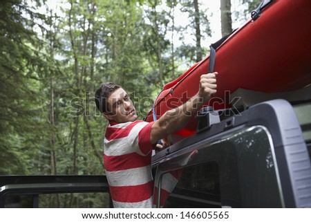 Side view of a young man tying kayak on car roof in the forest - stock photo