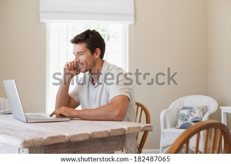 Side view of a young man using mobile phone and laptop at home - stock photo