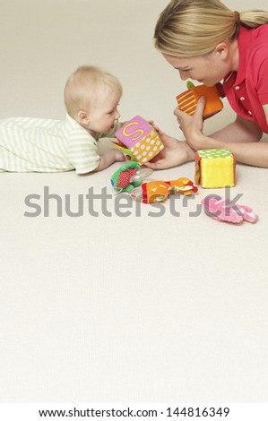 Side view of a young mother and child playing with toys on floor - stock photo