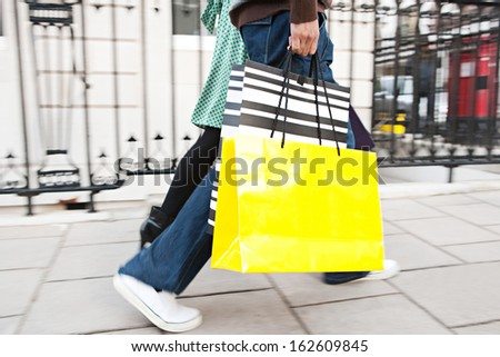 Side view of a young tourist couple on holiday walking down an exclusive shopping street in London with classic stone buildings and holding carrier paper bags, outdoors. - stock photo