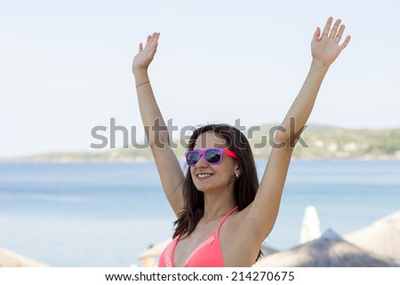 Side view of a young woman breathing fresh air while standing on a beach shore with her arms outstretched back, enjoying the intense blue sea and sky at sunset during a vacation. - stock photo