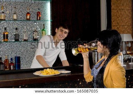 Side view of a young woman drinking a pint of beer in a nightclub with a smiling friendly bartender behind the counter - stock photo