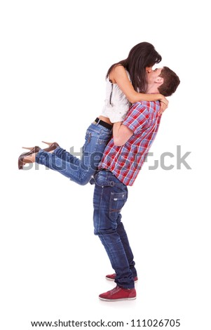 side view of a young woman in her boyfriend's arms kissing him romantically
