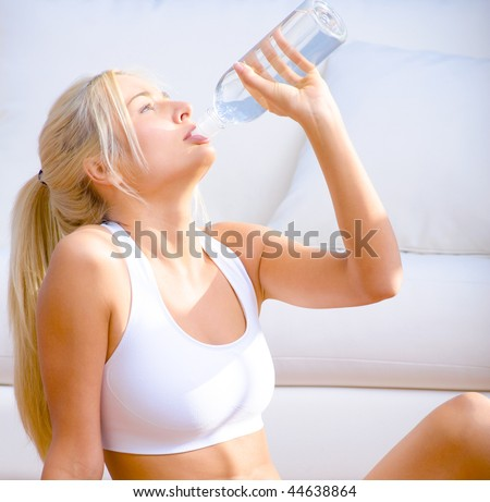 Side view of a young woman in sportswear drinking bottled water.  Square shot. - stock photo