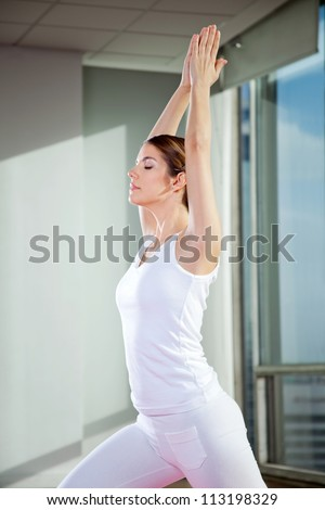 Side view of a young woman performing Crescent Moon pose at gym - stock photo