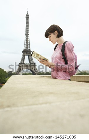 Side view of a young woman reading book on balcony against Eiffel Tower