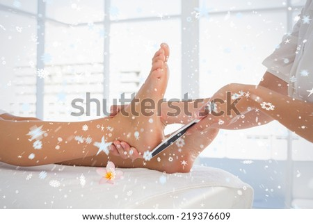 Side view of a young woman receiving pedicure treatment against snow - stock photo