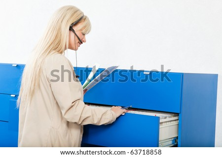 Side view of a young woman searching for documents through a file drawer - stock photo
