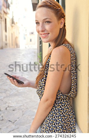Side view of a young woman sightseeing visiting a picturesque stone pavement street, using a smartphone mobile to network, smiling in a destination city on summer holiday, outdoors. Travel technology.