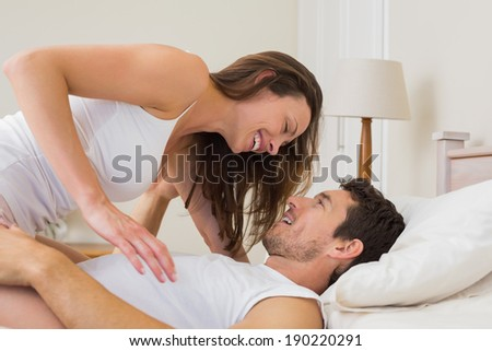 Side view of a young woman sitting on man in bed at home