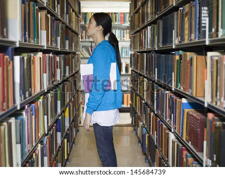 Side view of a young woman standing by bookshelf in library
