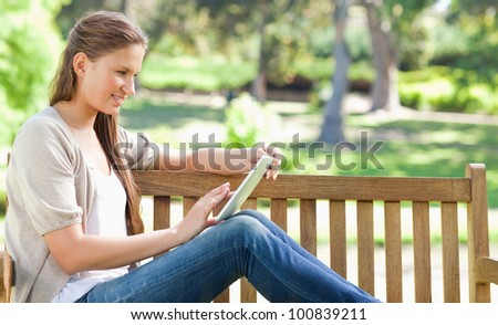 Side view of a young woman using a tablet computer on a park bench - stock photo