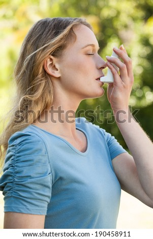 Side view of a young woman using asthma inhaler at the park - stock photo
