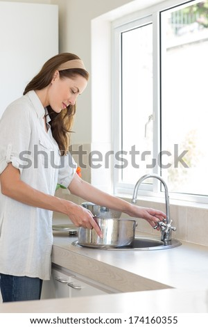Side view of a young woman with vessel at the washbasin in the kitchen at home