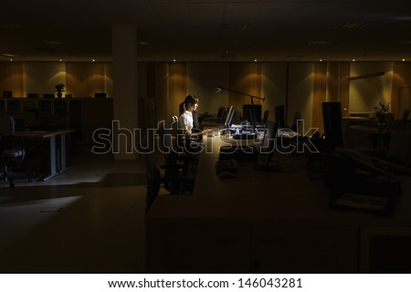 Side view of a young woman working on computer in dark office - stock photo