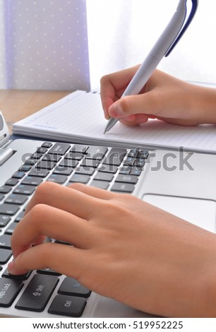 Side view of accountant's hands doing paperwork on cork desktop and laptop keyboard