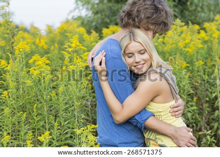 Side view of affectionate couple hugging in field - stock photo