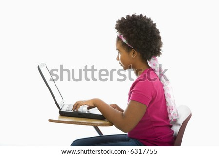 Side view of African American girl sitting in school desk typing on laptop computer. - stock photo