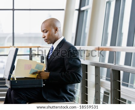 Side view of African businessman reviewing files in briefcase in office lobby