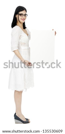Side view of an adult (early 30's) woman, wearing a lovely white summer dress and holding a blank sign next to her while looking at the camera with a large toothy smile. Isolated on white background. - stock photo