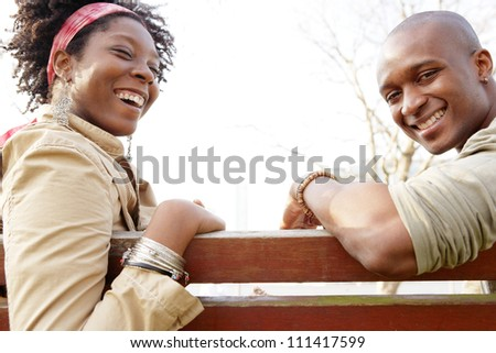 Side view of an african american couple sitting on a wooden bench against the sky, laughing together. - stock photo