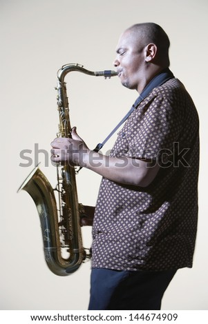 Side view of an African American man playing saxophone against gray background - stock photo