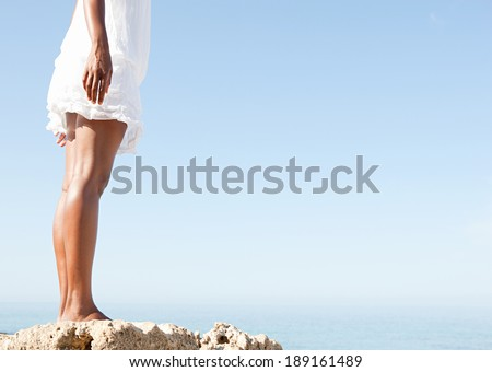 Side view of an attractive african american black woman legs standing on a natural coastal rock high up, contemplating the sea against a blue sky on holiday with the feeling of escapism, lifestyle. - stock photo