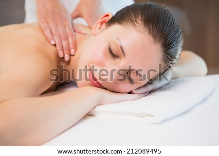 Side view of an attractive young woman receiving back massage at spa center