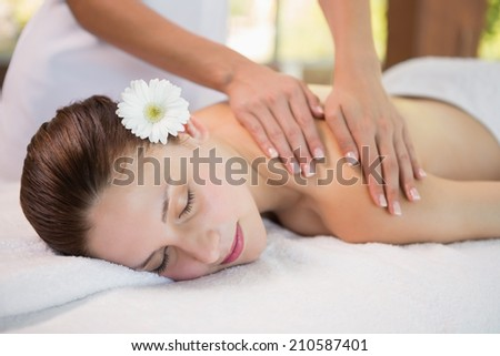 Side view of an attractive young woman receiving shoulder massage at spa center - stock photo
