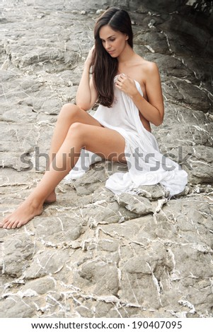 Side view of an attractive young woman relaxing on a gray textured rock face on a beach, wearing a white sarong and being thoughtful and serene during a summer holiday. Beauty and lifestyle outdoors.