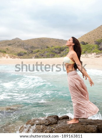 Side view of an attractive young woman stretching and relaxing standing on a rock by the sea, breathing fresh air in a beach and enjoying nature. Beauty outdoors lifestyle.