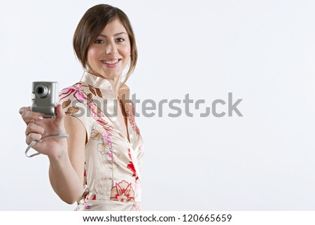 Side view of an attractive young woman using a digital photographic camera while standing isolated against a plain white background, smiling at the camera. - stock photo