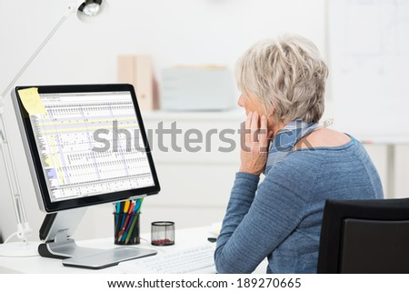 Side view of an elderly businesswoman working at her desk in the office studying a spreadsheet on a large desktop monitor - stock photo